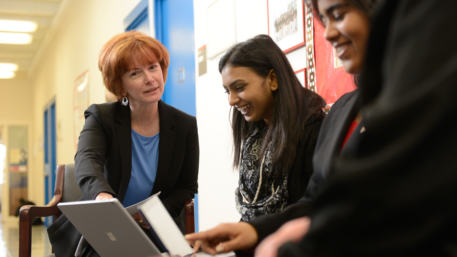 A faculty member talks with two students.