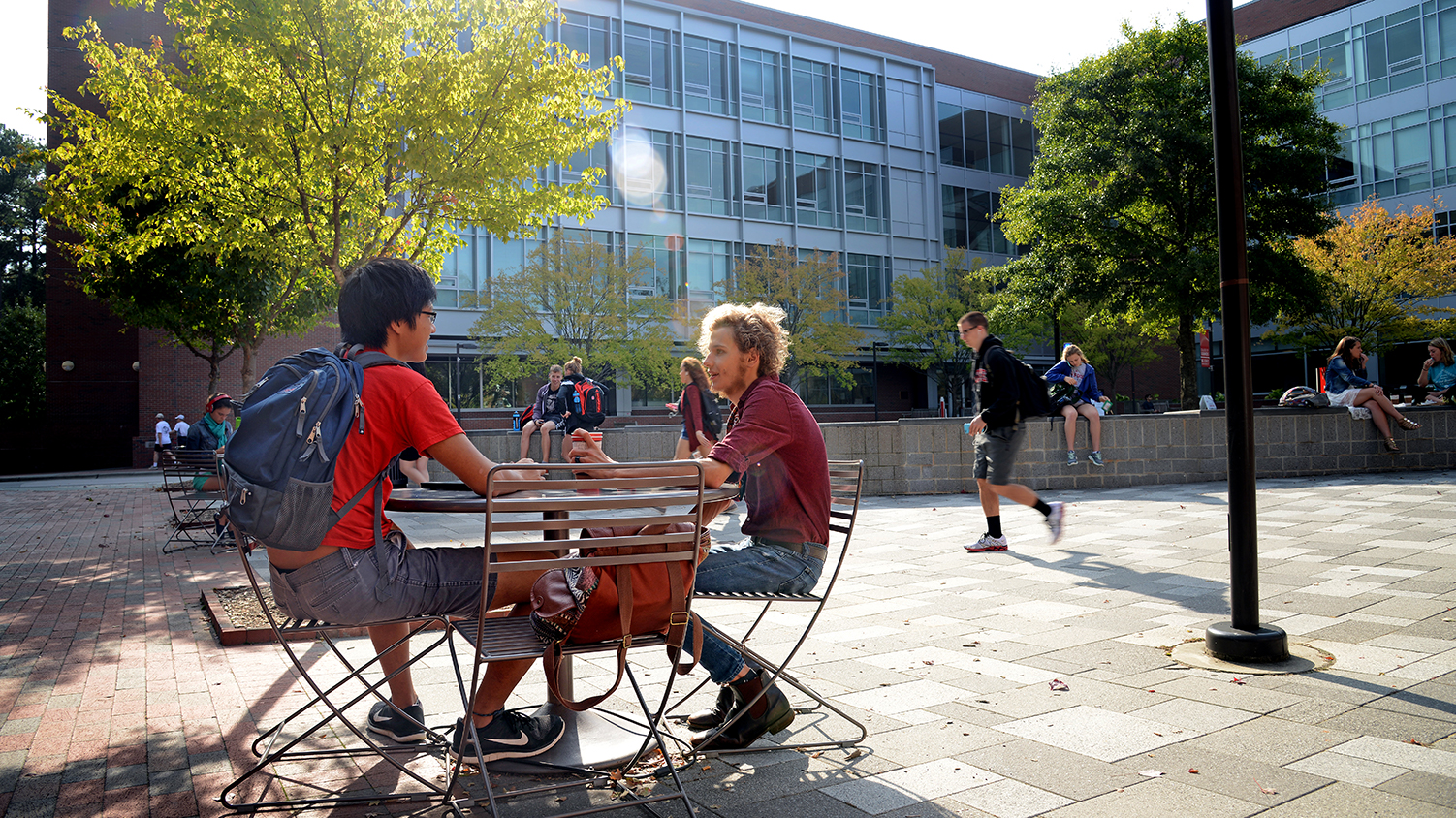 Two NC State students chat at an outdoor table on NC State's campus.