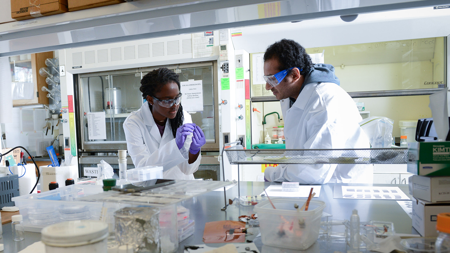 Two students in white lab coats examine a sample in a lab.