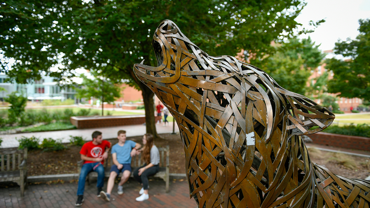A bronze wolf howls in Wolf Plaza on NCState's campus.