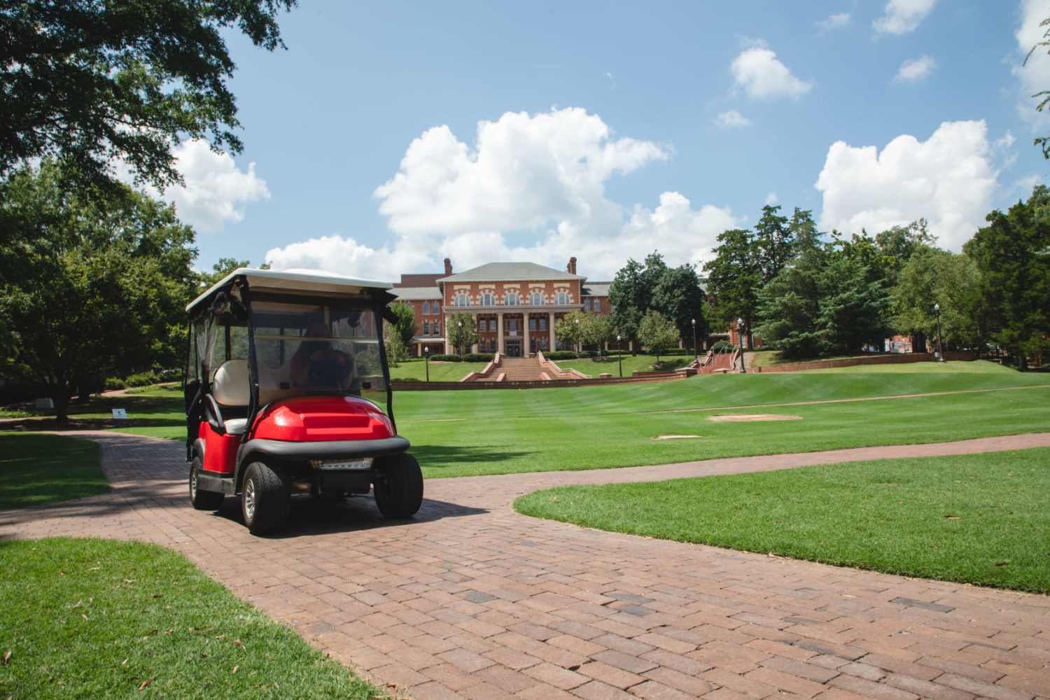 A red Wolfpack Pick Up golf cart drives along the brick path on the Court of Carolina