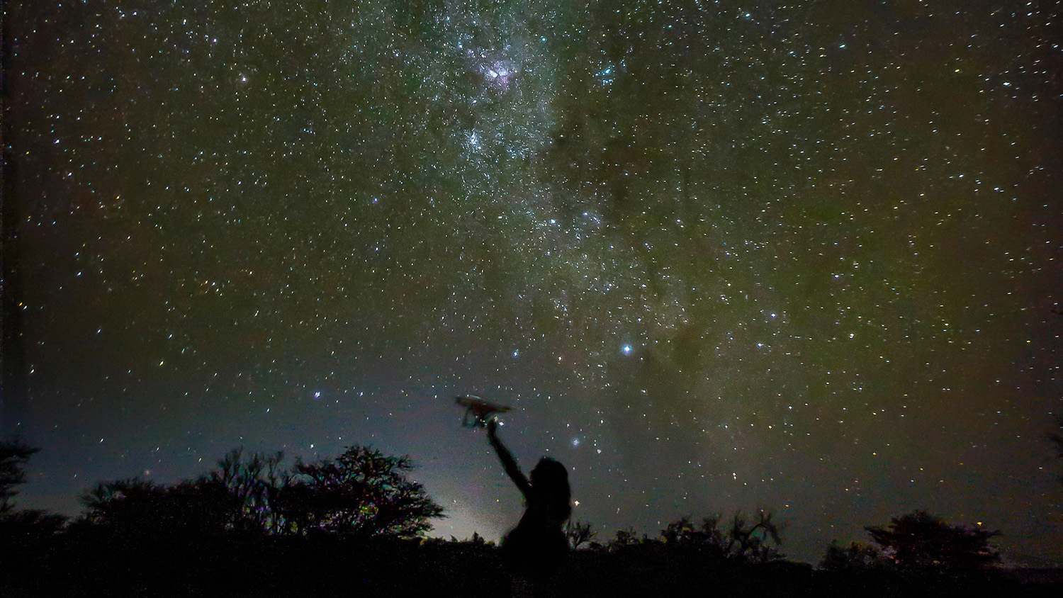 A researchers studying how drones can detect poachers and count wildlife in Namibia is juxtaposed against the Milky Way at night.