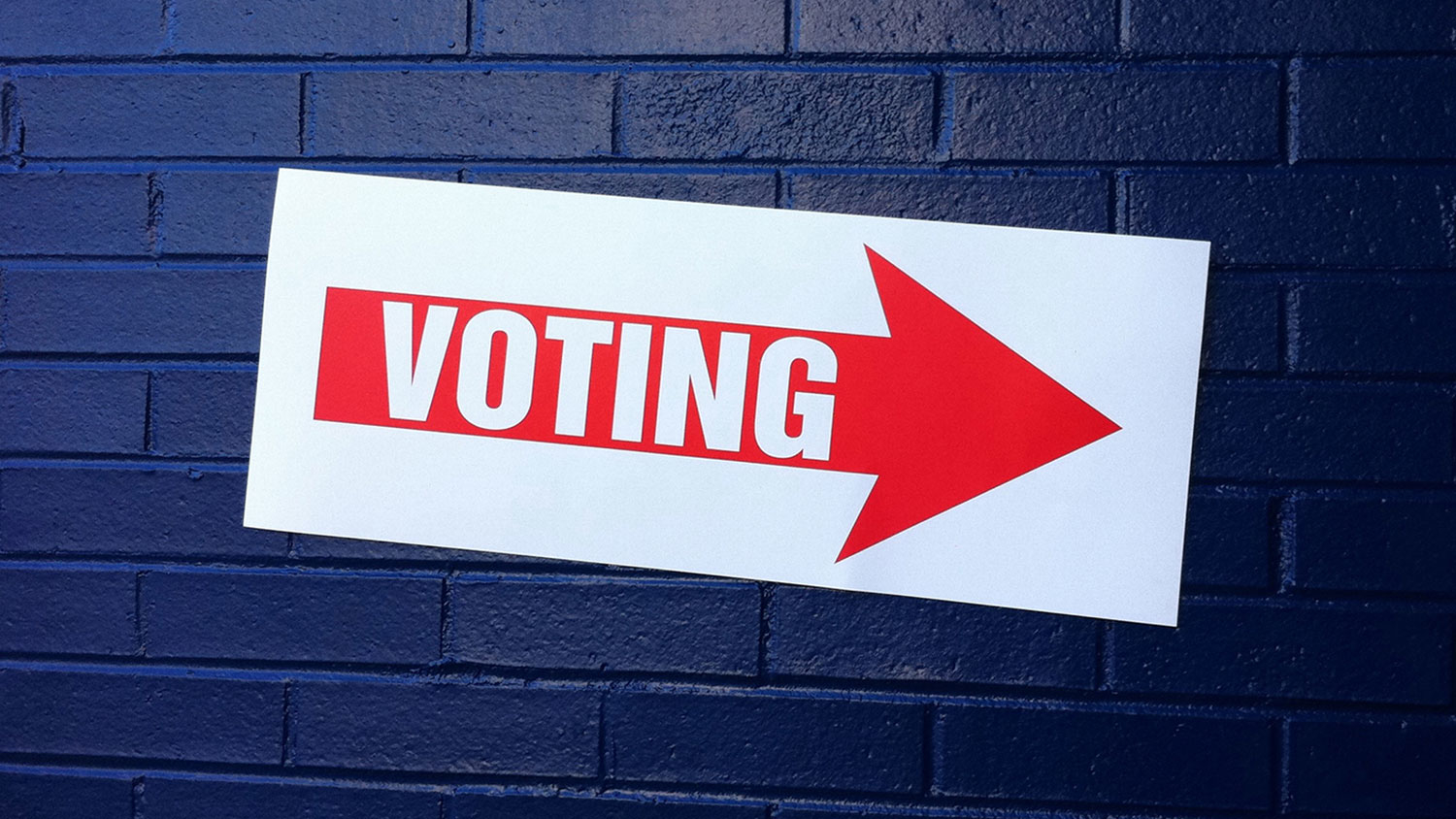 voting sign on a brick wall