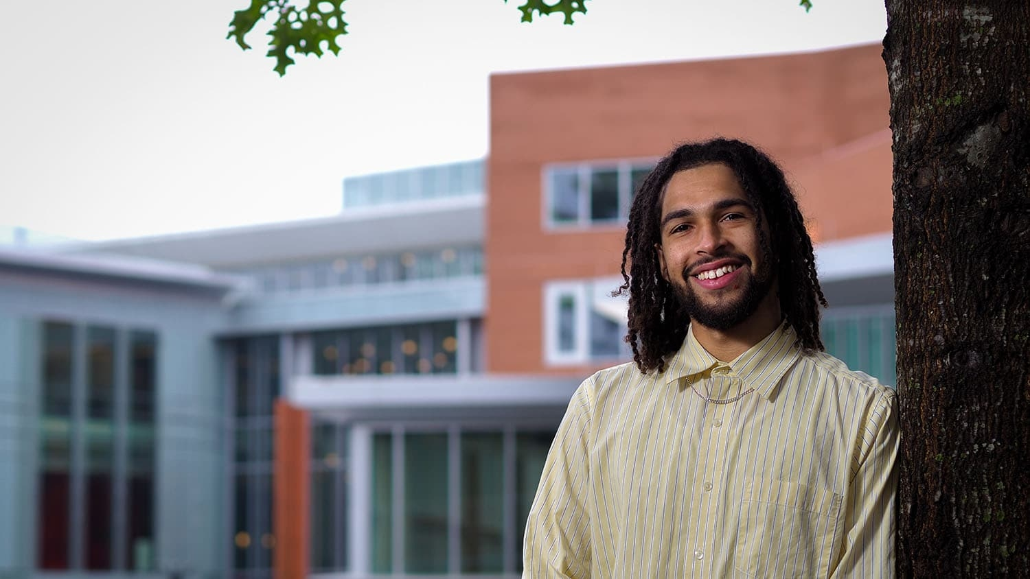 Gino Fernandes stands next to a tree with Talley Student Union in the background