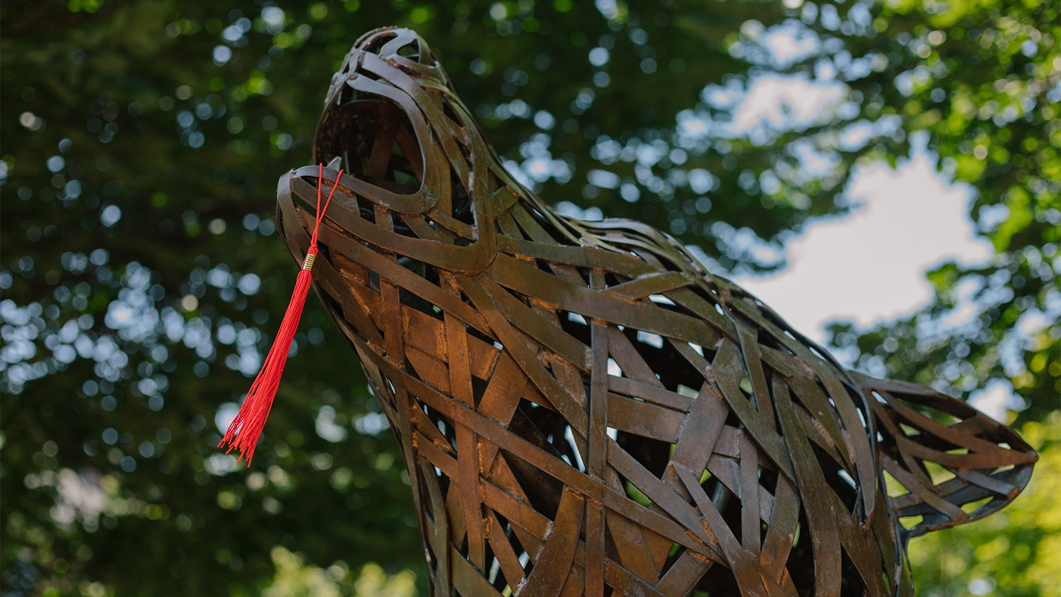 Wolf statue with a red tassel in its mouth