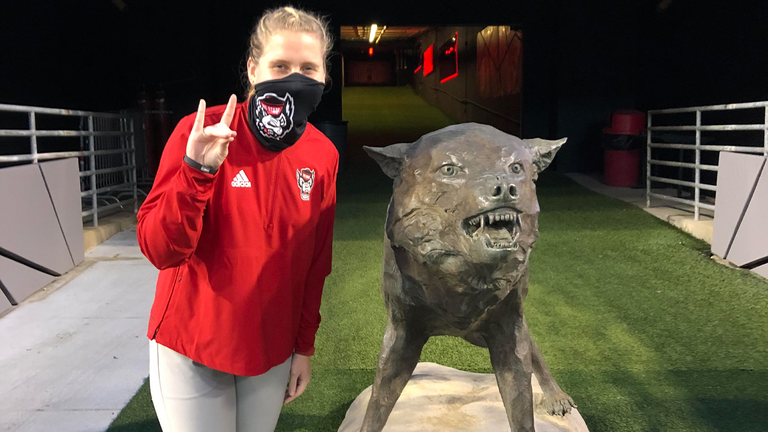 Crista Bain wearing a red jacket and a black NC State face mask makes a wolfie sign next to the wolf statue in Carter Finley Stadium