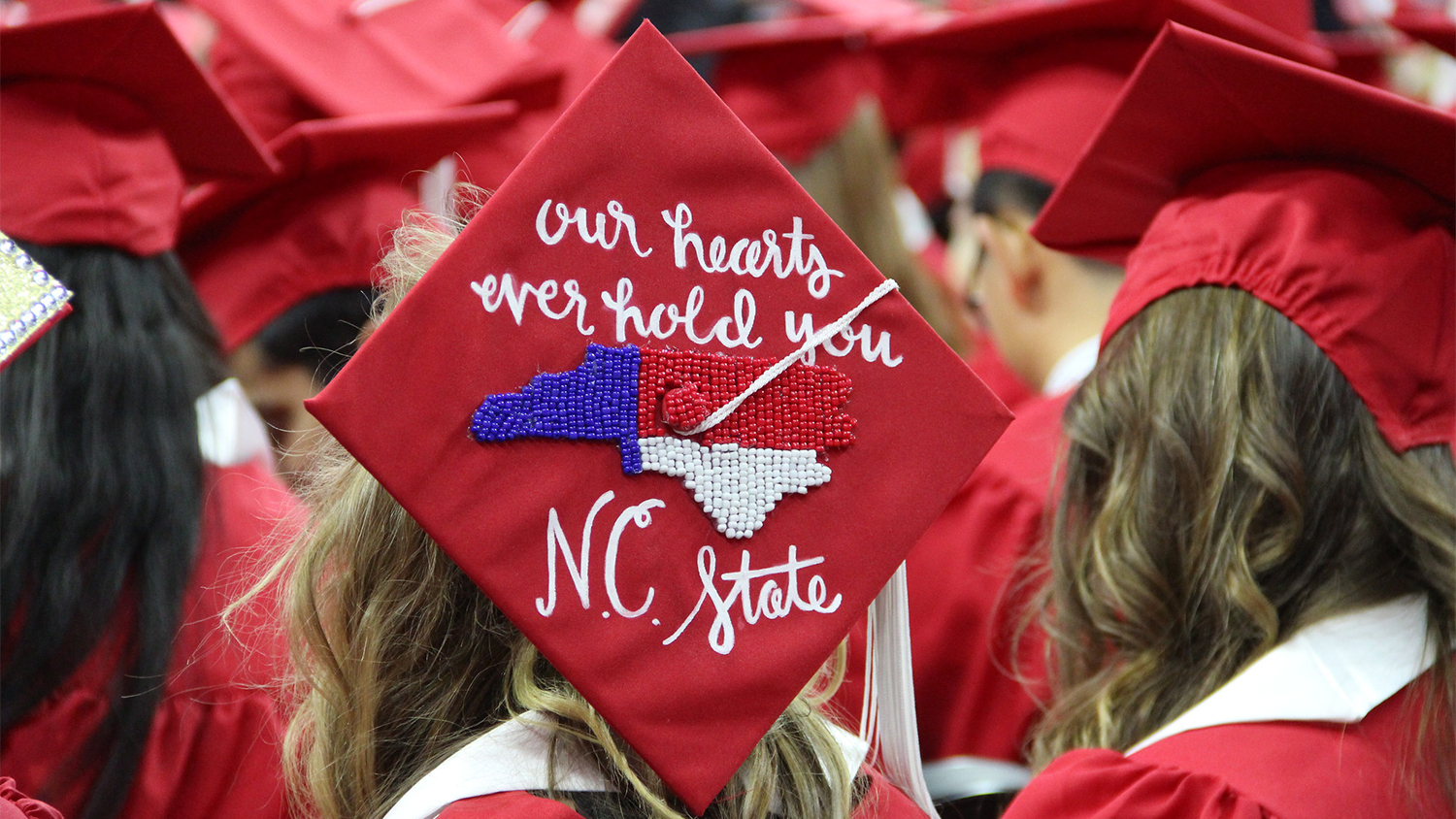"""The top of a graduate's hat that reads """"Our hearts ever hold you, NCState"""""""