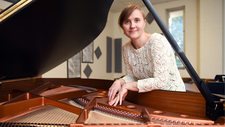 Olga Kleiankina leaning over a piano
