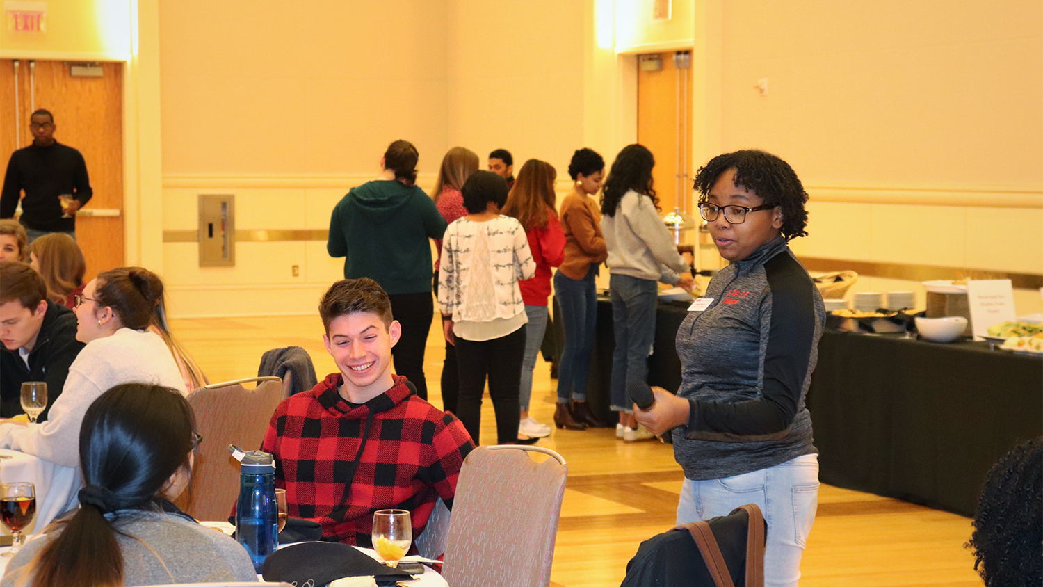 Sade Proctor speaks to students at a table during a career workshop