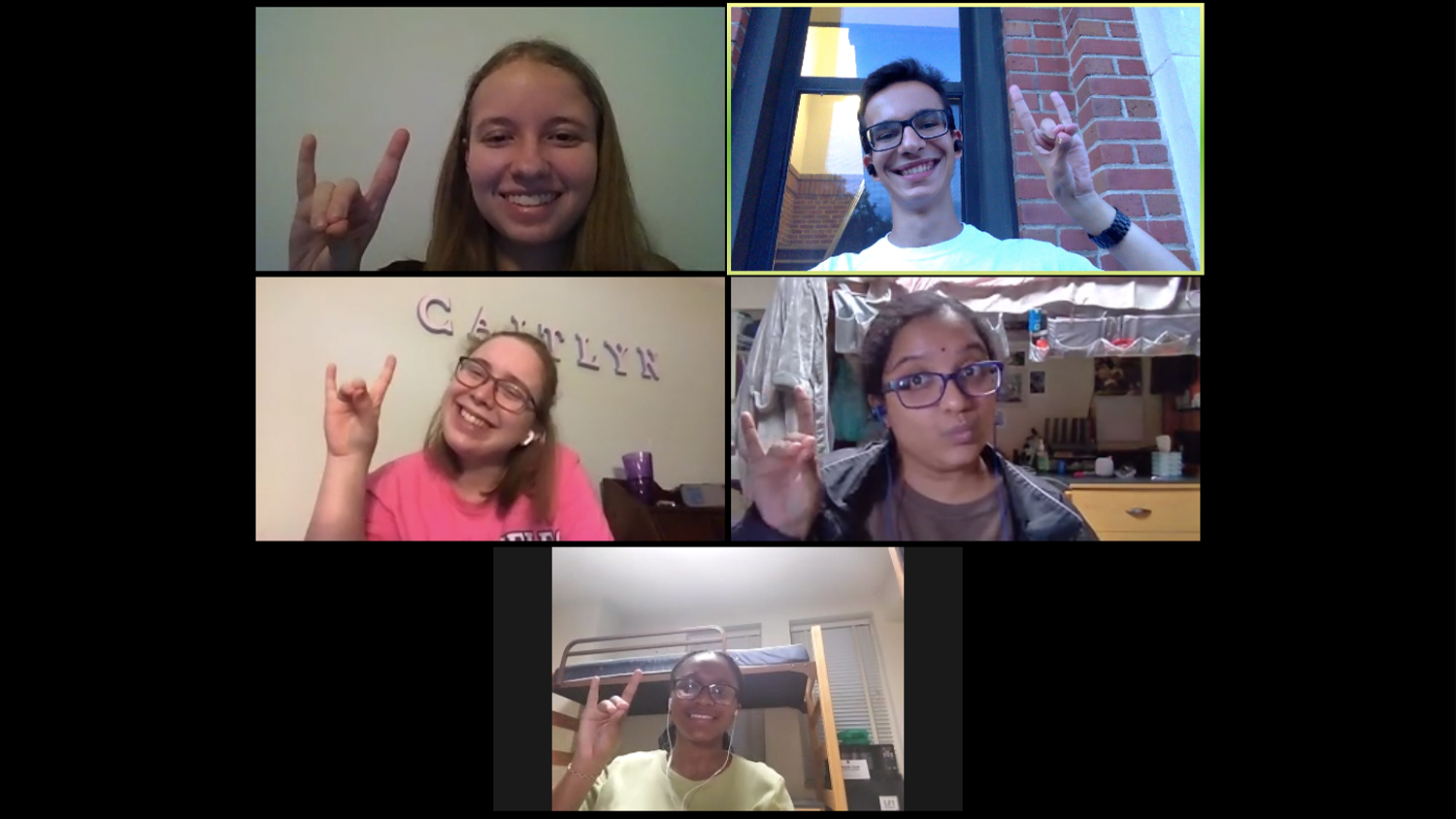 A screenshot of a Zoom video call, with five students make a wolfie sign through their windows