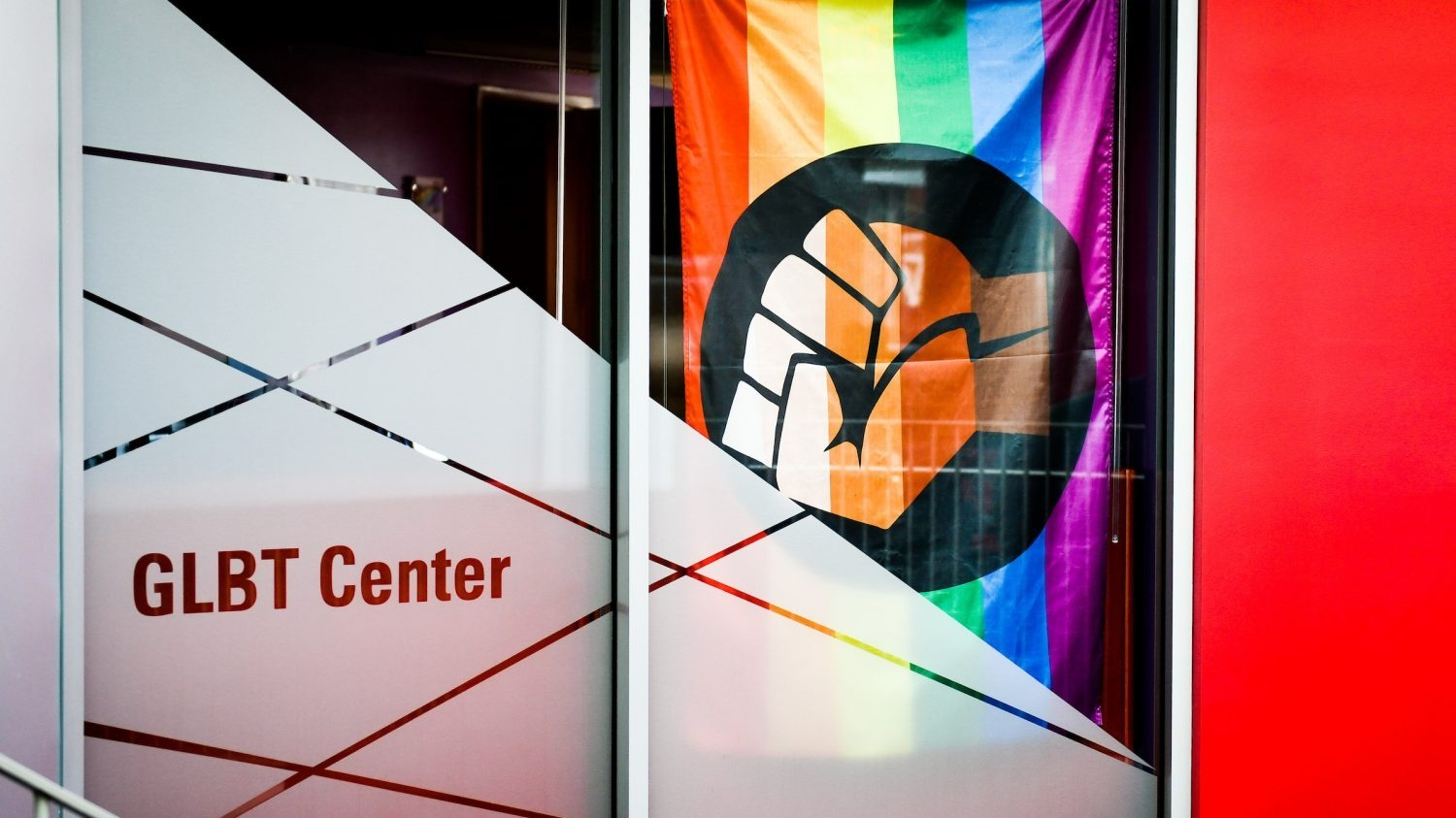 exterior shot of the GLBT center doors with the pride flag with raised fist hanging