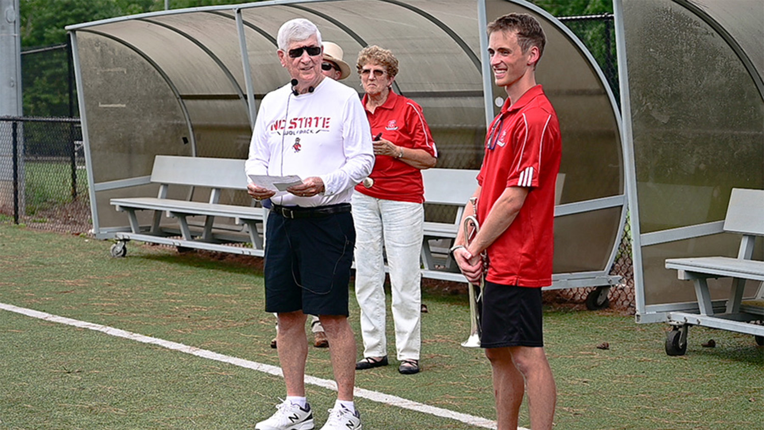 Gage Fringer, wearing a red shirt and black shorts and holding his trumpet, standing next to a man (Bob Masini) in a white shirt and black shorts
