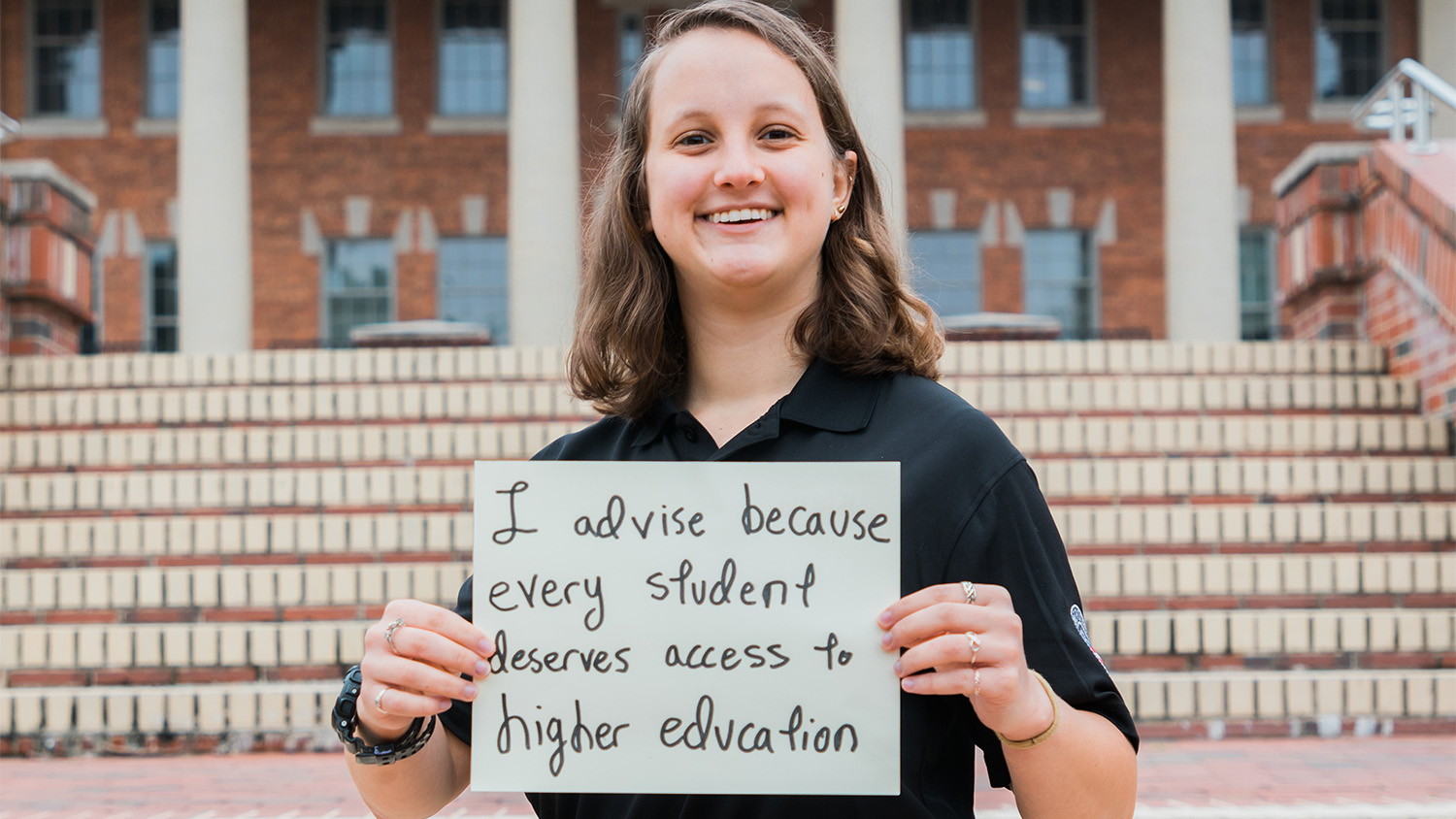 """Kiera Lindner holds a sign that reads """"I advise because every student deserves access to higher education"""""""
