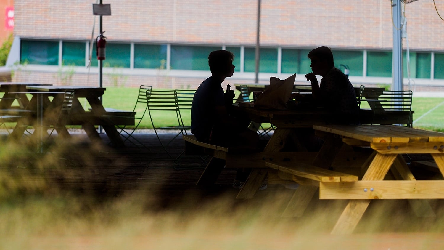 Two people, in shadows, talk at a picnic table on NC State's campus
