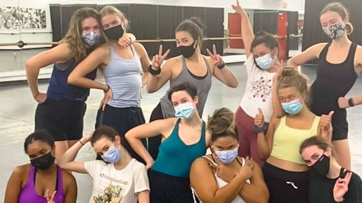 A group of dance students pose and make wolfie signs during the residency weekend
