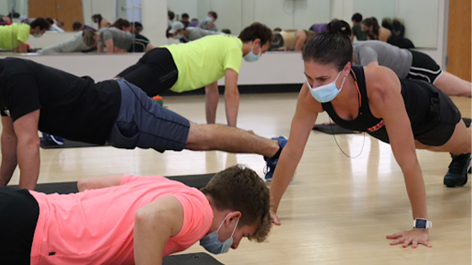 Renee Harrington and her students do pushups during class